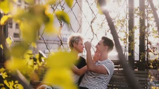 Slow motion relaxed smiling young man and woman talking on autumn park bench enjoying beautiful sunny day outside.