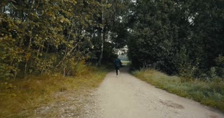 Slow motion runner on dark autumn forest road. Drone back view. Motivated lifestyle athlete going through hard moments.
