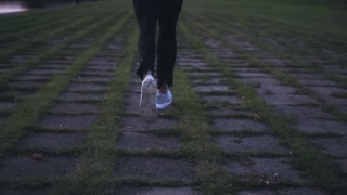 Slow motion running on grass tiles to the city. Back view. Abstract background shot. Concept of pursuing life goals.