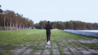 Slow motion. Sportsman enjoying healthy lifestyle. Background shot. Young man running on grass tiles. Back distant view.