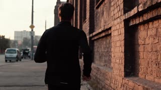 Slow motion sportsman running along old street. Young free determined professional runner morning workout. Back view