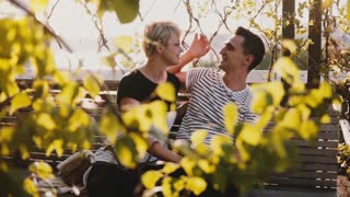 Slow motion sweet romantic couple sitting together having fun and talking on a park bench on beautiful sunny autumn day.