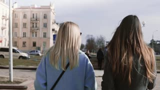 Slow motion two girls walk together in the street. Young ladies in stylish clothes with beautiful long hair. Back view.