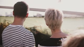 Slow motion unrecognizable man and woman stand near big fish tank with water and sea weed. Romantic couple on a date.