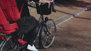 Smiling Caucasian girl on a leisure bicycle ride. Slow motion close-up. Pretty happy woman with a basket of flowers.