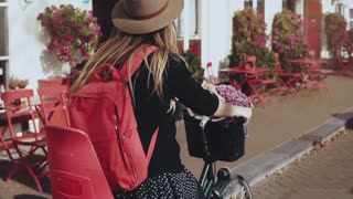 Smiling girl rides a bicycle with a red backpack. Slow motion close-up. European woman rides along street with flowers.