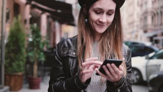 Smiling happy Caucasian female blogger in stylish hat walking along a street using smartphone shopping app slow motion.