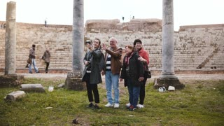 Smiling senior family and young woman tourists waving on video call to family at old amphitheater ruins in Ostia, Italy.