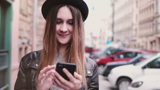 Smiling young European woman in stylish hat walking along city street with a smartphone looking forward slow motion.