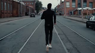 Sportsman running in the middle of the street. Background shot. Slow motion. Back distant view between tram tracks.