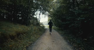 Sportsman running on dark autumn forest road. Young athlete on quiet autumn deserted pass. Cinematic drone back view.