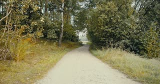 Sportsman running to a forest road opening. Drone back view. Sprinter enjoying quiet autumn countryside pathway.