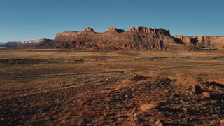 Static drone shot of American canyon mountain ridge panorama, car taking off small parking in the middle of the desert.