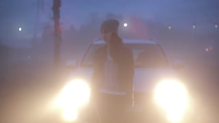 Stressed Caucasian girl standing near headlights. Worried female near broken car lost and worried on dark foggy highway.