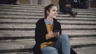 Student girl sitting in evening at the ladder and looking to someone, smile. Woman use smartphone, browse the Internet.