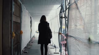 Student girl walking through the white construction corridor. Back view of young woman goes to work across the building.