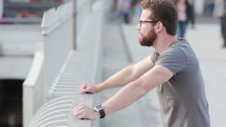 Stylish man standing on the bridge. Young businessman with beard and glasses have a break outside, looks at the city.