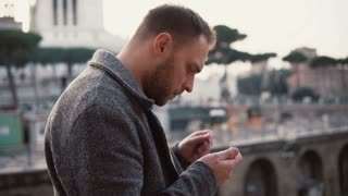 Stylish man stands at the centre of Rome, Italy. The handsome male uses smartphone, browse the Internet.
