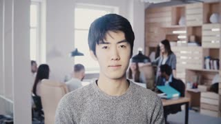 Successful Asian male start-up founder posing. Handsome businessman manager looking at camera in busy modern office 4K.