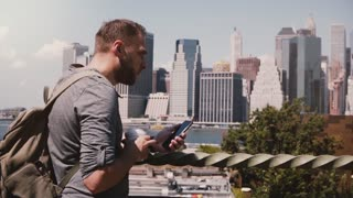 Successful Caucasian businessman with coffee standing and using smartphone at Manhattan skyline, New York, slow motion.