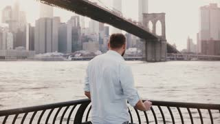 Successful happy businessman stands near Brooklyn Bridge embankment fence panorama in New York City, back view 4K.