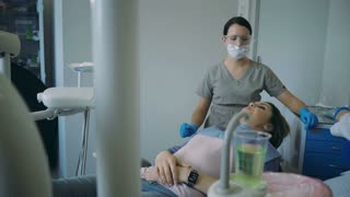 The end of dental treatment, doctor lifts up the dental chair. Young female visiting dentist for check-up oral cavity.