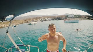 The young man falls backwards into the water, waves the hand goodbye from the deck of the ship. Summer holiday in sea.