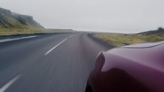 Time lapse: close-up view of front fender of red car going through countryside road. Vehicle traveling on high speed.