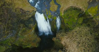 Top aerial top view of the waterfall Gljufrabui in Iceland. Copter moves down, flow of water falls from the top.