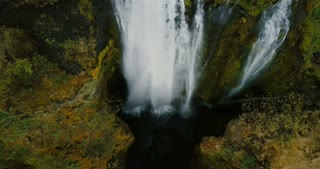Top aerial view of the beautiful Gljufrabui waterfall in iceland. Copter flying over flow of water falls down from cliff