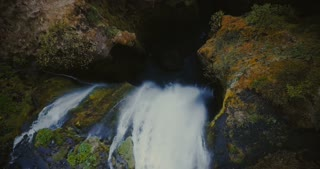 Top aerial view of the beautiful Gljufrabui waterfall in Iceland. Copter moving down, water falls between the mountains.