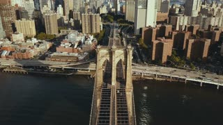 Top aerial view of the Brooklyn bridge through the East river to Manhattan in New York, America. Flag waving on the wind