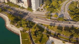 Top aerial view of the Chicago, America. Drone flying over Michigan lake, traffic road and apartments in the morning.