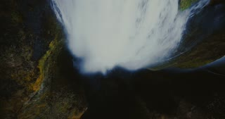 Top aerial view of the falling down water with splashes and foam. Scenic Gljufrabui waterfall in Iceland.
