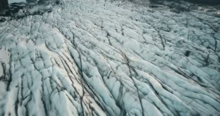 Top aerial view of the iceberg in Iceland. Drone flying over the stripes of glacier Vatnajokull with volcanic ash.