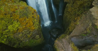 Top aerial view of the waterfall Gljufrabui in Iceland. Copter flying over the turbulent flow of river, water falls down