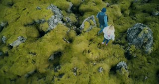 Top aerial view of the young beautiful couple walking on the lava field covered moss in Iceland, exploring the nature.