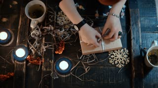 Top close-up view of female hands decorating the holiday box. Young woman preparing Christmas present to friend.
