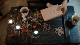 Top close-up view of female hands making gift sitting at the table at home. Woman binds a Christmas box with a ribbon.