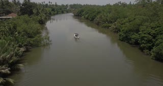 Top view drone getting close to little white boat cruising along big beautiful calm jungle river with green palm trees.