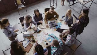 Top view of business team working at trendy loft office. Young mixed race group of people puts palm together on centre.