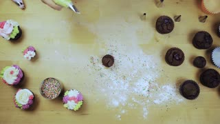Top view of female hands decorating the chocolate cupcakes. Young woman using the pastry bag for cream.