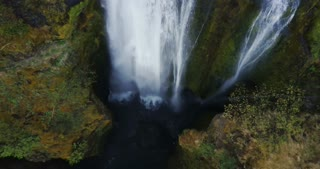 Top view of the beautiful waterfall Gljufrabui in Iceland. Copter moving up, water falls down from the top of mountain.