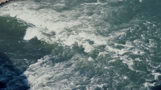 Top view of tropical sea waves with foam. Wild current, ocean surface. Top view to the blue water. Slow motion.