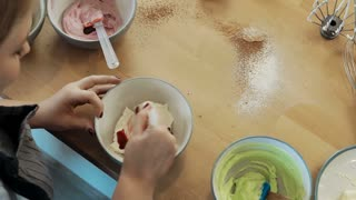 Top view of young blonde woman mixing the cream for decorating and dye in the bowl. Female cooking cupcakes.