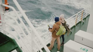 Top view of young couple standing on the board of the ship. Man and woman with action camera enjoying the view of sea.
