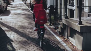 Tourist girl riding bicycle on sunny city street. Back view slow motion. Female on a bike with red backpack cruising.