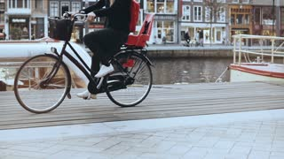 Tourist lady gets off a bicycle on river quay. European traveller female enjoying happy freedom moments. Slow motion.
