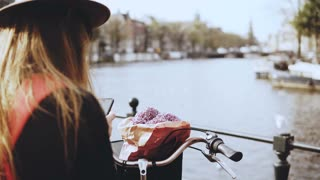 Tourist lady with bicycle takes photos on bridge. Female with long hair and flowers photographs beautiful river scenery.