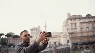 Tourist man takes selfie photos against the background of city centre of Rome, Italy with his smartphone, smiling.